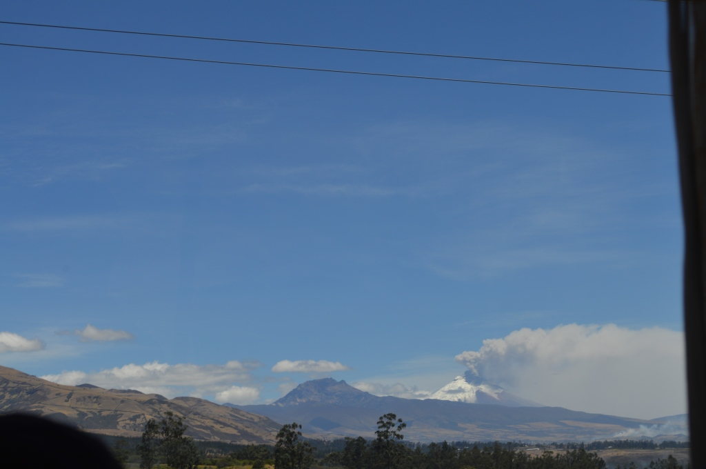Cotopaxi from a bus window. Hard to see from this picture but the snow is melted on half of it (in the direction the smoke is blowing)
